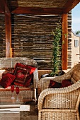 Suite of wicker furniture with red cushions below wooden pergola with bamboo screens