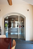 Round archway with open glass door and view into designer kitchen
