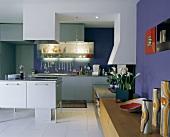 Designer Küchenblock mit Dunstabzug vor Küchenzeile in offenem Wohnraum mit Sideboard an blauer Wand