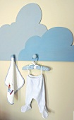 Dolls' clothes on coathanger hanging on wooden pegboard in the shape of a cloud