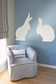 Upholstered armchair in front of wall painted with rabbit motif in nursery