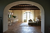 Rustic country house with designer furnishings - view through wide arched doorway into open-plan living and dining room