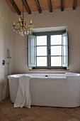 Designer bathtub in front of window and brass chandelier in renovated bathroom of country house