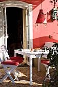 Weisser Tisch, weisse Klappstühle mit roten Sitzkissen & rote Hängeleuchte auf teilweise überdachtem Balkon