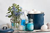 An arrangement of grape hyacinths, dye and eggs