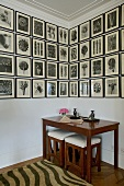 Gallery of black and white drawings above Biedermeier table with matching stools in corner of room
