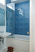 Corner of bathroom with bathtub and shower head against blue-tiled wall