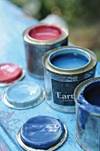 Three opened cans of paint