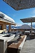 Gedeckter Tisch auf Holzterrasse einer Hütte in verschneiter Berglandschaft