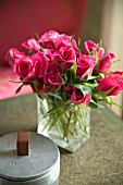 Bouquet of pink roses in glass vase and ceramic box with lid