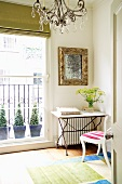 Table with metal frame and stone top in corner of room next to balcony door with view of potted plants
