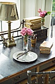 Breakfast plate and antiquarian books in front of posy of roses on desk