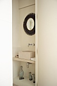 Niche in bathroom containing modern wash basin and framed mirror
