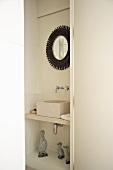 Niche in bathroom containing modern wash basin and framed mirror