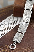 Silver link bracelet made with embossed floral pattern