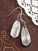 Hand made, silver earrings with embossed pattern on a leather surface