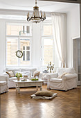 Sofa set with white loose covers and coffee table below chandelier in bay window of living room in period apartment