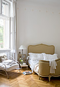 French Corbeille bed and iron armchair on herringbone parquet in bedroom of period apartment