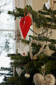 Christmas tree decorated with various heart-shaped ornaments and fairy lights