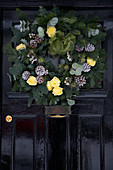 Christmas wreath with silver-painted pine cones and yellow roses on old front door