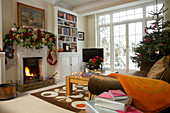 Living room in English country house with eclectic furnishings and festively decorated with fir tree and garland of roses
