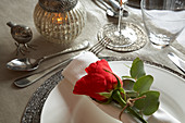 Festive place setting with silver accessories and red rose on rolled napkin