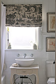 Wash basin on top of antique-style cabinet below window; Roman blind printed with Chinese motifs