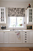 Simple, country-house-style kitchen unit with wall-mounted cupboards and sink below window with grey, patterned Roman blind