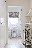 Dressing room in hallway with fitted wardrobe and ornate towel rail; view of washstand in ensuite bathroom
