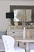 Loose covered chair at round dining table; lamp with silver base and male bust decorating vintage chest of drawers in background