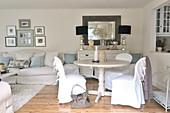 Weisses Wohnzimmer im romantisch eleganten Landhausstil mit Hussenstühlen an rundem Esstisch neben Durchreiche zur Küche