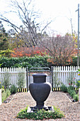 Fountain made from anthracite-coloured amphora on gravel garden path and view of road beyond white wooden fence