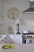 Nostalgic wall-mounted clock, wrought iron lamp base and pyramid of pigs decorating white, country house kitchen