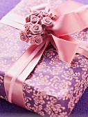 A gift box decorated with a bow and roses