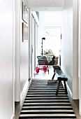 Narrow hallway with black and white striped runner and view through open door of vintage tricycle in modern living room