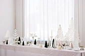 Christmas decorations on long table below window with closed curtain