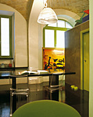 Simple Italian designer style - black multifunctional table with plexiglass chairs and cubic room-in-room installation placed in historic brick vault