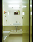 View of bright, simple designer bathroom through open door painted lime green