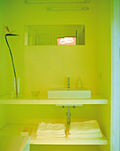 Bathroom niche bathed in yellow light with square counter-top basin on open washstand with towel shelf