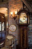 Antique grandfather clock next to upholstered chair and sconce lamp on brick wall