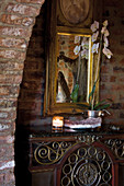 Potted orchid on antique console table and gilt-framed mirror on brick wall