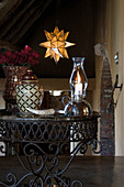 Candle lantern and urn on wrought iron side table in rustic foyer