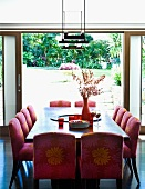Upholstered chairs with patterned covers at dining table in front of open terrace door showing view of garden