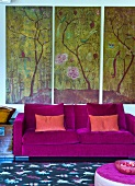 Modern couch with violet velvet cover against triptych of landscape motifs on wall