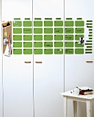 Calender made of green magnetic wafers on white cabinet fronts