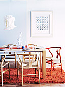 Table, designer chairs, pendant lamp with paper lampshade and wool rug in dining room