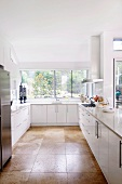 White designer kitchen with large, light brown floor tiles