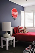 Modern teenager's bedroom with table lamp on bedside table next to bed against dark grey wall