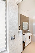 Small, polygonal tiles on wall with shower fittings in modern bathroom
