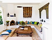 Moroccan-Greek elements in a living room with a masonry fireplace and upholstered seating